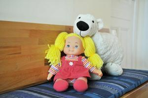 Puppe und Eisbär sitzen lächelnd auf der Bank